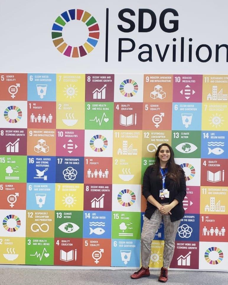 Rocío Parra posando en un mural de un encuentro medio ambiental donde se lee SDG Pavilion