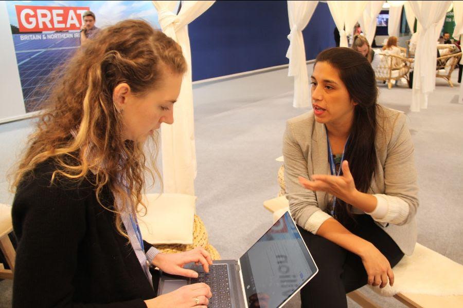 Rocío Parra conversando con alguien que tiene un computador en el encuentro medio ambiental de la COP25.